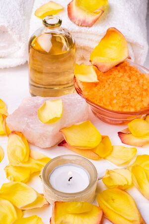 Wellness center. Composition with orange-flavored bath salts, transparent glass bottle with perfumed essential oil, white towels, rose petals and candle.