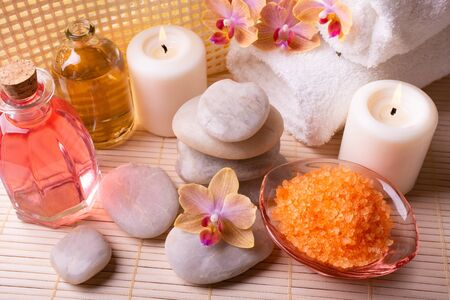 At the center of the table are the orchids and stacked stones, white towels, aromatic bath salts, some candles and transparent bottles with perfumed essences. Stock fotó