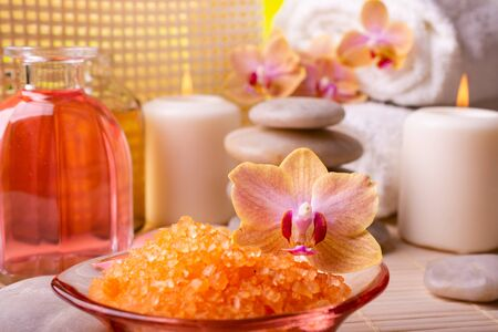 Wellness center. In the foreground, an orchid and orange-flavored bath salts. In the background candles, stacked stones, white towels and bottles with perfumed essences