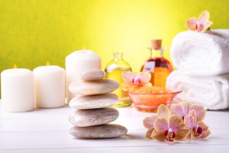 At the center of the white table are the orchids and stacked stones, in the background, white towels, bath salts, some candles and transparent bottles with perfumed essences.