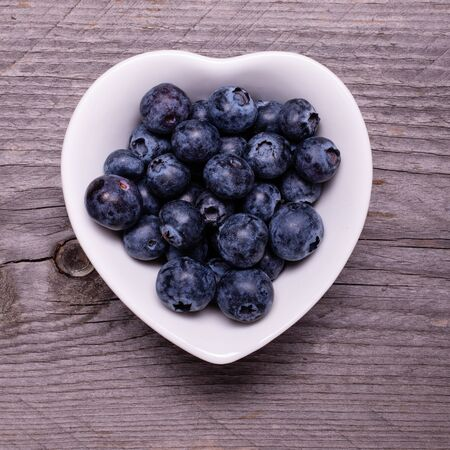 in the white ceramic heart-shaped bowl, ripe blueberries, in the foreground, against the background of rough wood