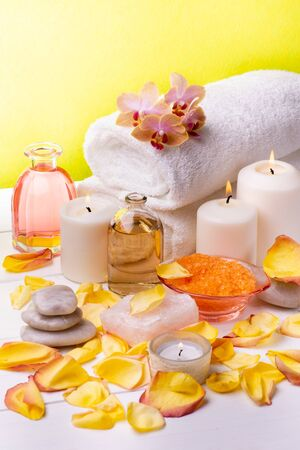 At the center of the table are the transparent bottles with oil and perfumed essences, orange-flavored bath salts, white towels, rose petals, orchids, some stones and candles.