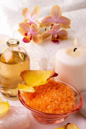 Spa. Featured orange-flavored bath salts, clear glass bottle with perfumed essential oil, white towels, rose petals, orchids, stones and candle.
