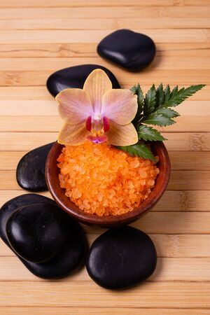 bowl with fragrant bath salt, a single orchid, a fern leaf, and some black stones for massage. View from above Stock fotó