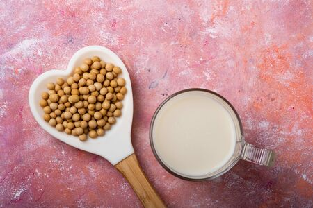 seen from above, on a rustic background, a glass with soy milk, and soy beans in the heart-shaped spoon.