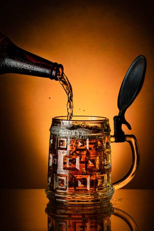 fresh beer poured from the bottle into the glass mug on the golden background Stock fotó