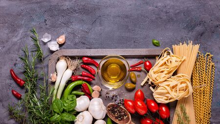top view, on a rustic dark gray background, raw pasta and traditional Italian ingredients with olive oil, various vegetables and spices