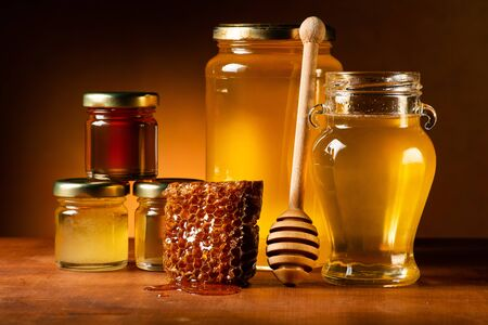 Various types of honey in glass jars with ladle and honeycomb. Still life