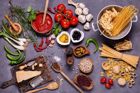 top view, on a dark rustic background, raw pasta and traditional Italian ingredients with olive oil, parmesan, vegetables, legumes and various types of spices Banco de Imagens