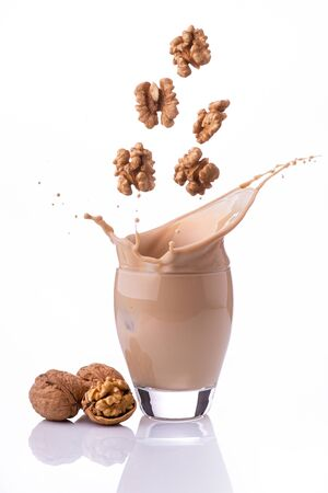 in the glass, isolated from the white background, a vegetable drink of nuts, with a splash