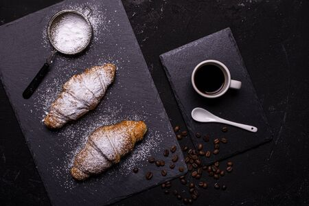 top view, cup of black coffee and croissants with veiled sugar on a dark background