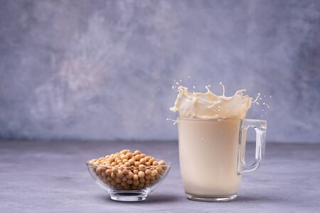On gray background rustic, the glass of soy milk with splash and yellow soy beans