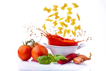 isolated from the white background, the raw Italian pasta in the shape of a butterfly falls into the pan with tomato sauce