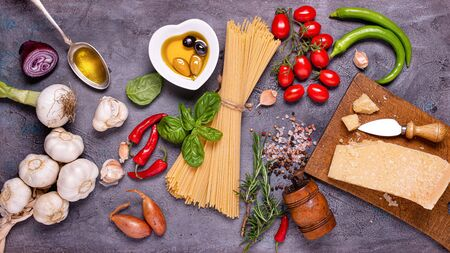top view, on a dark gray rustic background, Italian spaghetti with olive oil, seasoned cheese, bunch of tomatoes, various vegetables and spices