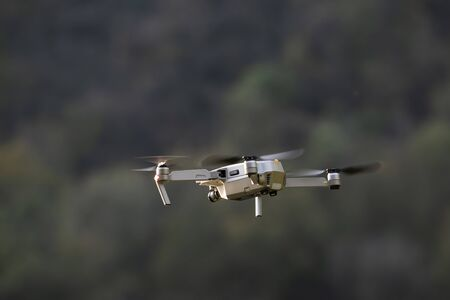 Drone in flight, in the foreground, with a video camera, surrounded by nature