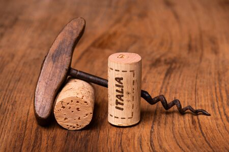 in the foreground, on raw wood, Italian wine corks and vintage corkscrews