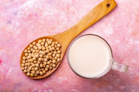 seen from above, on a rustic background, a glass with soy milk, and soy beans in the wooden spoon