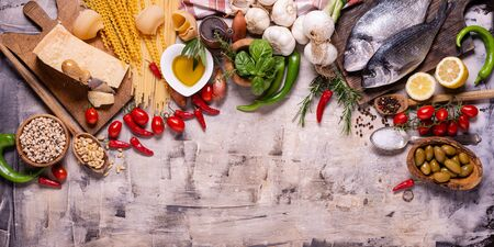 top view, on a rustic background raw pasta and traditional Italian ingredients with olive oil, parmesan, vegetables, fresh fish, legumes and various kinds of spices