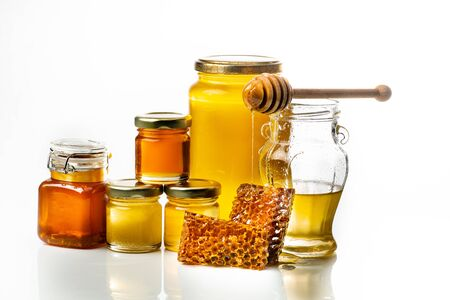 Various types of honey in glass jars with ladle and honeycomb. White background