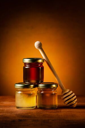 on the rustic table various types of honey in glass jars with ladle. Still life Banco de Imagens