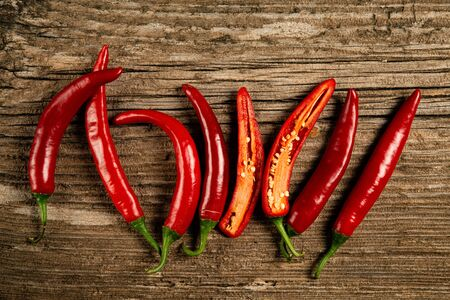 red and spicy chillies on the rough wooden table, with top view