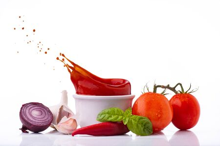isolated from the white background, fresh vegetables and ingredients and a pan with tomato sauce with splash