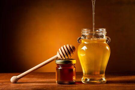 fluid honey flows into the glass jar. dead nature Banco de Imagens