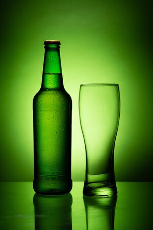 a bottle of beer with condensation and an empty glass isolated on the green background