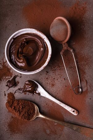 top view, ceramic bowl with dark chocolate cream, spoon covered with chocolate and sprinkling of cocoa on the background Stock fotó