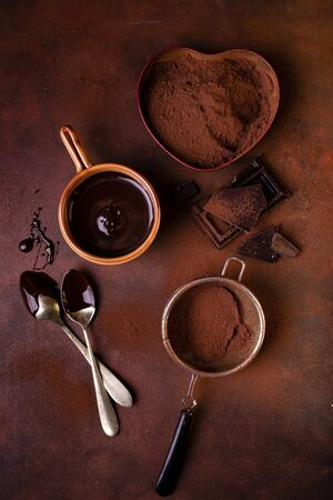 still life with top view, brown background, sprinkled with chocolate and cocoa powder, a bowl with melted dark chocolate.