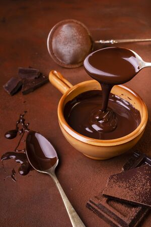 brown background, smeared with cocoa and chocolate chips, some pieces of chocolate and a bowl with melted dark chocolate Stock fotó