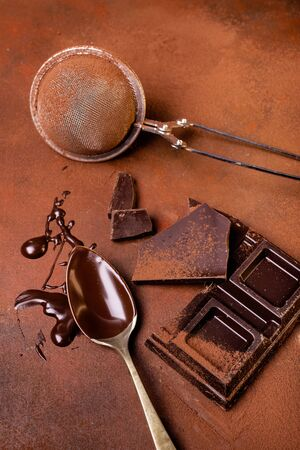 still life with top view, on the rough brown background, sprinkled with cocoa powder, a few pieces of chocolate and a spoon smeared with melted chocolate