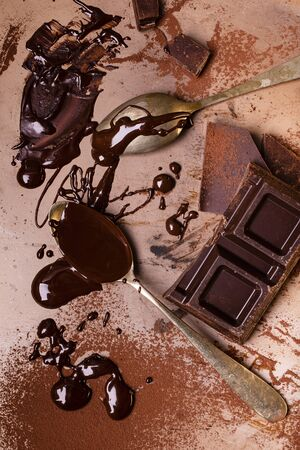 still life with top view, on the background of raw metal, sprinkled with cocoa powder, some pieces of chocolate and a spoon smeared with melted chocolate