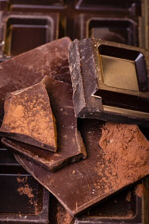 in the foreground stacked pieces of dark chocolate sprinkled with cocoa powder. Stock fotó