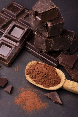 wooden spoon with cocoa powder and pieces of dark chocolate.