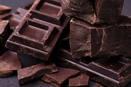 im Vordergrund gestapelte dunkle Schokoladenstücke, die mit Kakaopulver bestreut sind.