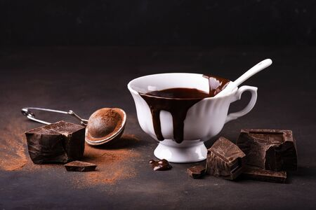 on a dark rustic surface, a cup of hot chocolate, a few pieces of dark chocolate and cocoa powder