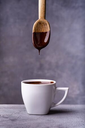 in the foreground, hot and liquid chocolate pouring from the spoon into a white ceramic cup