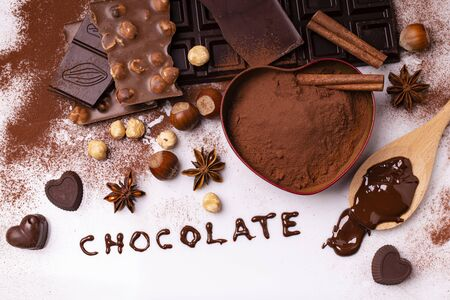 heart-shaped bowl with cocoa powder, some types of chocolate with hazelnuts and spices