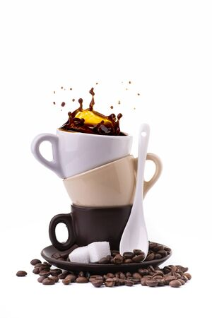 isolated from the white background, a saucer with three different colored coffee cups from which a splash of black coffee is generated.