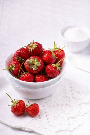 on the textured white tablecloth, in the foreground, a white ceramic bowl with ripe and bright red strawberries