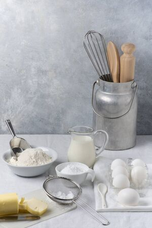 in the kitchen on the gray textured background, some utensils, flour, milk and eggs and various ingredients ready for the preparation of homemade culinary recipes
