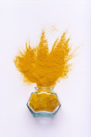 from the glass bowl a sprinkling of turmeric on a white background. seen from above