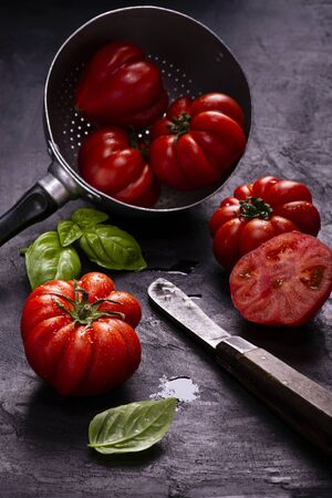 in the foreground, on a textured black background, some ripe and fresh tomatoes, basil leaves and an old knife used to halve the tomato. Still life