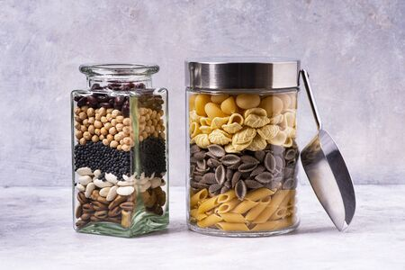 On a gray textured background, varieties of Italian pasta and dried legumes in glass jars in the foreground. Mediterranean diet Zdjęcie Seryjne