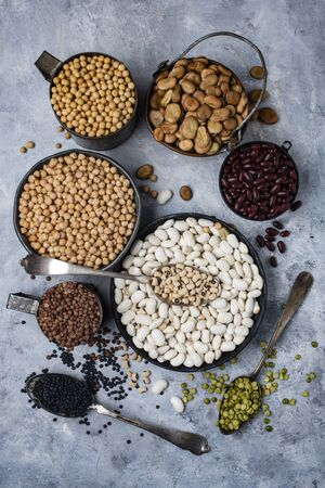 top view, in different bowls, on a textured gray background, variety of raw and colorful dry legumes rich in protein