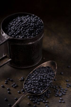 on a textured brown background, in the foreground, a spoon and a rustic metal cup with dried black lentils, rich in protein. copy space. still life