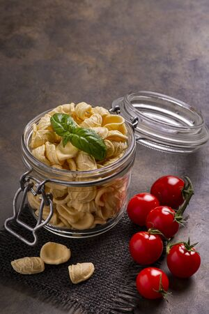in the foreground in a transparent glass jar of raw Italian pasta and fresh basil leaves. in the background bunch of cherry tomatoes Zdjęcie Seryjne