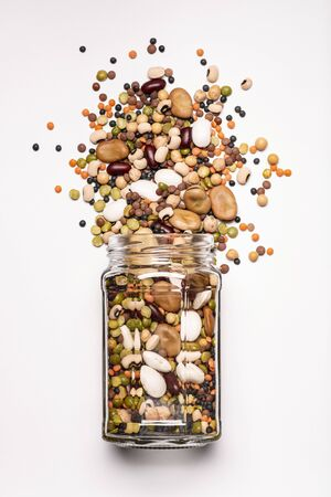glass jar with a large variety of dried legumes in the foreground, top view, isolated from the white background