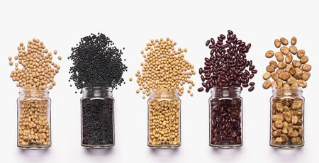 glass jars arranged in a row with variety of dried legumes in the foreground, top view, isolated from white background